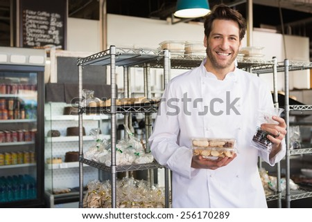 Cheerful baker holding coffee house and food at the bakery - stock photo