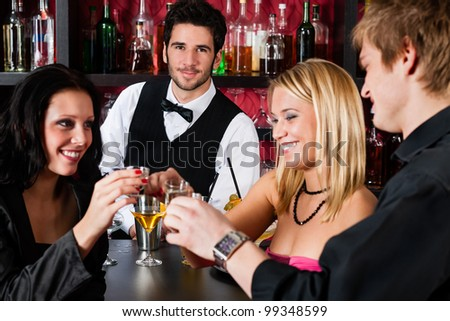 Cheerful barman behind counter with young friends at cocktail bar - stock photo