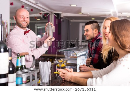 Cheerful bartender mixing cocktails for clients at bar - stock photo