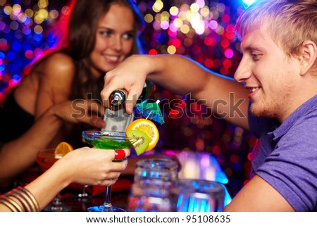 Cheerful bartender pouring cocktails at a birthday party - stock photo