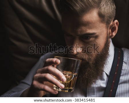 Cheerful bearded businessman is drinking expensive whisky - stock photo
