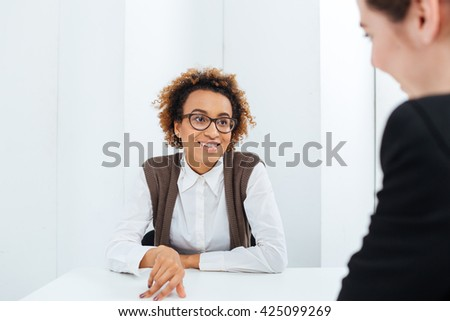 Cheerful beautiful african american young businesswoman interviewing candidate for new position in office - stock photo