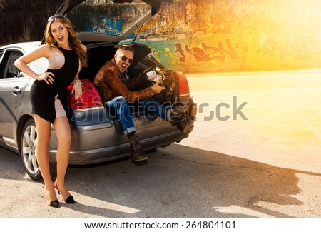 cheerful beautiful couple enjoys a bag full of money sitting in the trunk of a car outdoors - stock photo