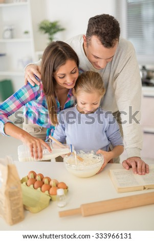 Cheerful beautiful family enjoying while preparing food in the kitchen.
