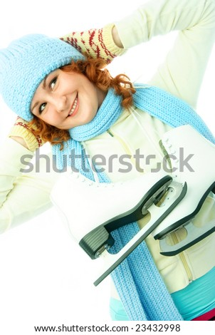 cheerful beautiful ginger girl dressed in warm winter clothes goes ice-skating - stock photo