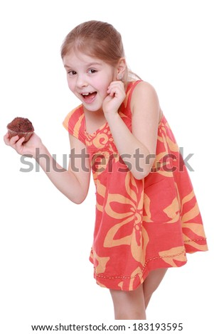 Cheerful beautiful little girl holding small chocolate cupcake isolated over white background/Happy kid holding chocolate cupcake - stock photo