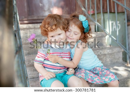 cheerful beautiful red children stand near the wall on a sunny day and smiling - stock photo