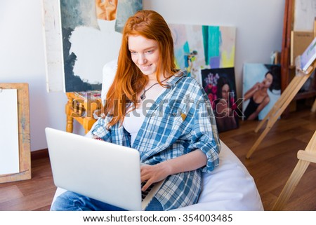 Cheerful beautiful redhead young woman sitting on soft white beanbag and using laptop in drawing class - stock photo
