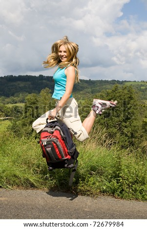 Cheerful beautiful woman hold backpack and jumping on way. Funny teen girl in nature runs with bag. Happy student jumps on the way.