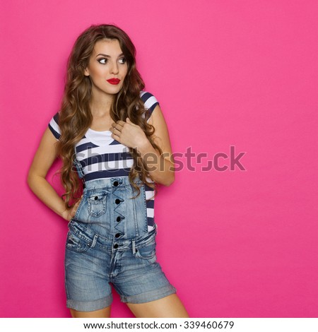 Cheerful beautiful woman in dungarees looking away at copy space. Three quarter length studio shot on pink background. - stock photo