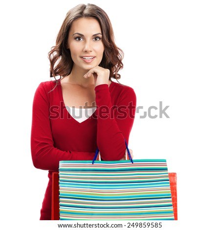 Cheerful beautiful woman in red casual clothing with shopping bags, isolated over white background - stock photo