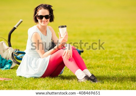 Cheerful beautiful woman relaxing outside with a cup of coffee standing on grass in the park - stock photo