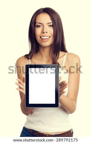 cheerful beautiful young brunette woman in tank top casual smart clothing, showing empty blank no-name tablet pc monitor, with copyspace area for slogan or text - stock photo
