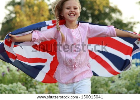 Cheerful beautiful young girl running with the flag of the UK in the summer garden