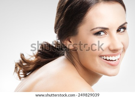 Cheerful beautiful young smiling woman, against grey - stock photo