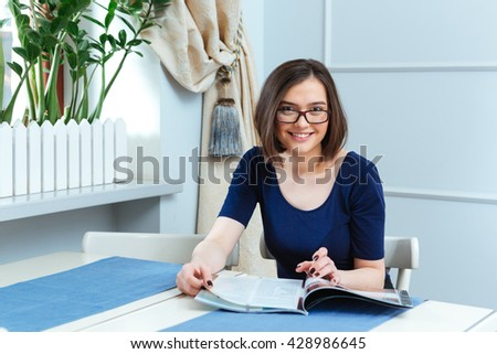 Cheerful beautiful young woman in glasses sitting and reading magazine in cafe  - stock photo