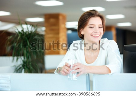 Cheerful beautiful young woman standing with glass of water in office - stock photo