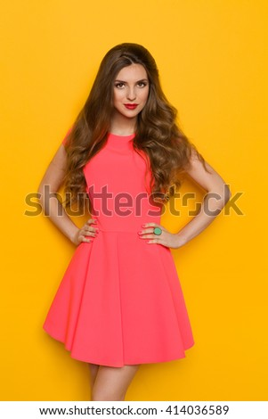 Cheerful beautiful young woman with curly long brown hair posing in pink mini dress and holding hands on hip. Three quarter length studio shot on yellow background. - stock photo