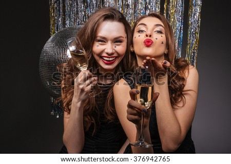 Cheerful beautiful young women having party and sending kiss over black background - stock photo