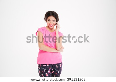 Cheerful beautiul young woman standing and talking on cell phone over white background - stock photo