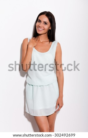 Cheerful beauty. Beautiful young woman in blue dress looking at camera and smiling while standing against white background - stock photo