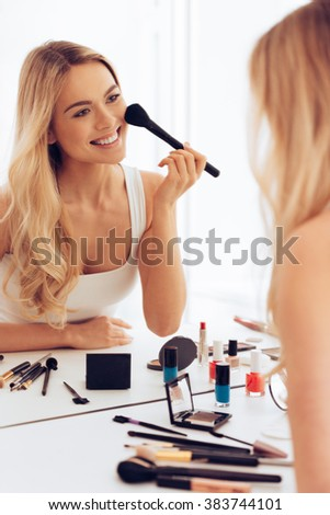 Cheerful beauty. Cheerful young woman applying make-up and looking at her reflection in mirror while sitting at the dressing table - stock photo