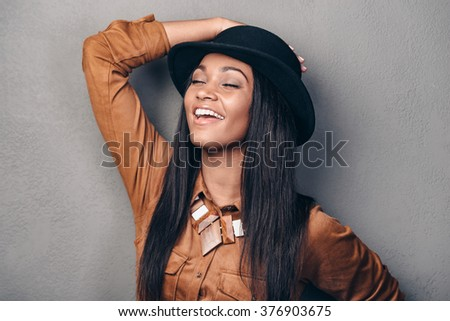 Cheerful beauty. Portrait of beautiful young cheerful African woman in hat keeping eyes closed and smiling while standing against grey background - stock photo
