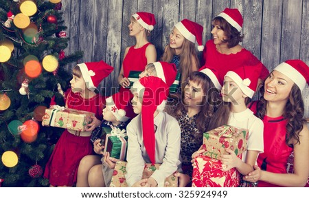 Cheerful big family  with gifts next Christmas tree looking  aside