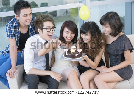 Cheerful birthday girl cutting a chocolate cake to share with her friends