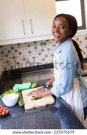 cheerful black woman cooking diner in kitchen - stock photo