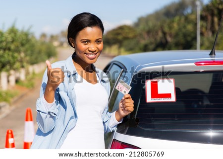 cheerful black woman showing a driving license she just got - stock photo