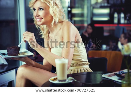 Cheerful blond beauty in a coffee shop - stock photo