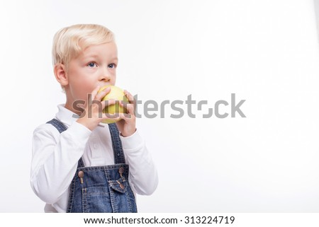Cheerful blond boy is biting a healthy apple with appetite. He is standing and looking forward with joy. Isolated and copy space in right side - stock photo
