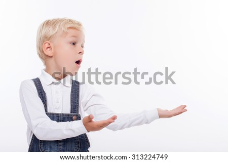 Cheerful blond boy is standing and raising his hands sideways. He is showing something. The boy is looking aside with surprise. Isolated and copy space in right side - stock photo