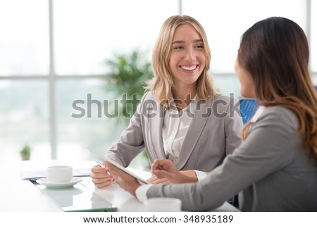 Cheerful blond business lady talking to her colleague in the office - stock photo