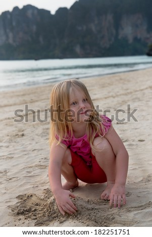 Cheerful blond hair girl play in sand at the beach - stock photo