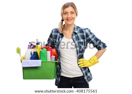 Cheerful blond housewife holding a bunch of cleaning products and looking at the camera isolated on white background - stock photo