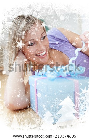 Cheerful blond woman holding a present lying on the floor against snow falling - stock photo