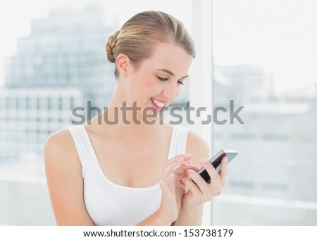 Cheerful blond woman in bright room text messaging - stock photo