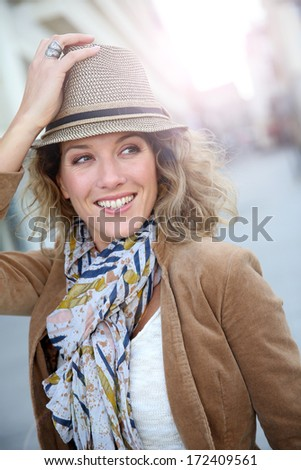 Cheerful blond woman in town with hat on - stock photo