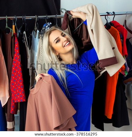 cheerful blonde chooses clothes and smiling. Happy young lady with a lot of clothing. Shopping concept. - stock photo