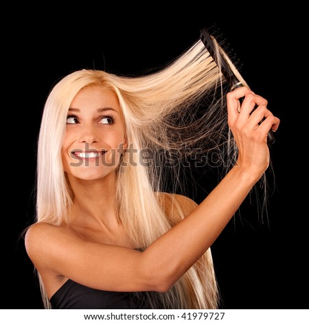 Cheerful blonde combs hair, it is isolated on black background.