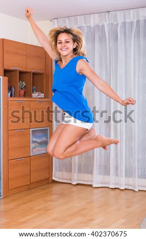 Cheerful blonde female jumping at home after receiving good news - stock photo