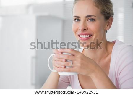 Cheerful blonde having coffee in her kitchen - stock photo