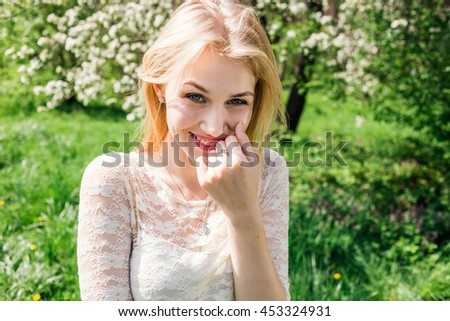 Cheerful blonde in blooming garden. Girl clothed white dress. Closeup. - stock photo
