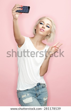 Cheerful blonde is photographed on the phone on a pink background - stock photo