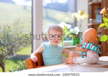 Cheerful blonde toddler girl feeding with yogurt her dolls sitting on a high chair indoors in sunny kitchen with garden view window - stock photo