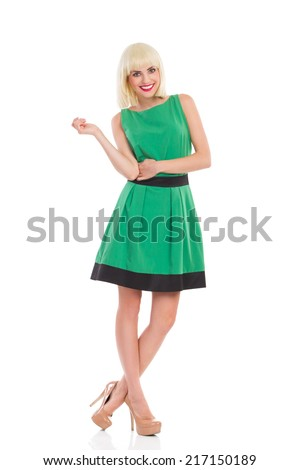 Cheerful blonde woman in green dress. Fashionable smiling blonde woman posing in green dress. Full length studio shot isolated on white. - stock photo