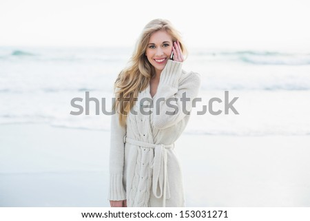 Cheerful blonde woman in wool cardigan making a phone call on the beach - stock photo
