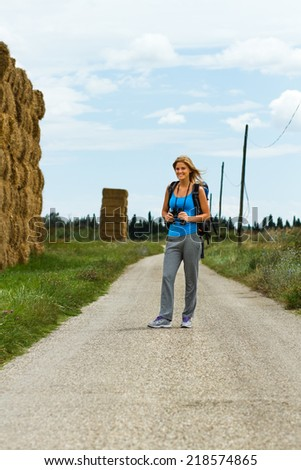 Cheerful blonde woman with backpack and binoculars enjoys walking the country road,Walk the country road